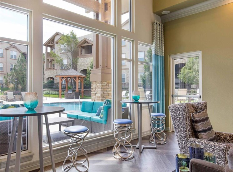 Clubhouse Lounge Area with Bar Height Tables and Stools Next to Window Overlooking Pool