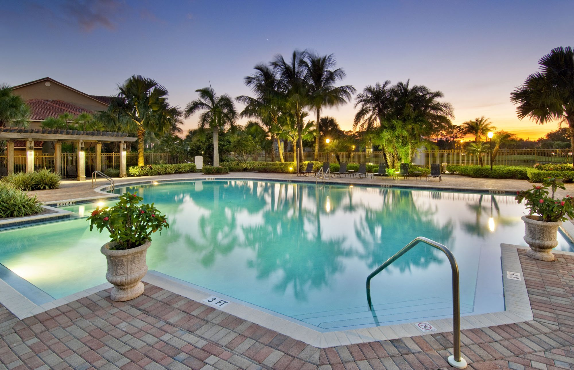 Swimming pool at dusk with sundeck and potted plants with clubhouse and palm trees in the background
