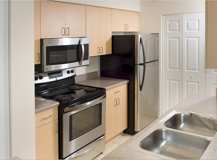 Fully Equipped Kitchen with Stainless Steel Appliances, Blonde Cabinets and Grey Counters