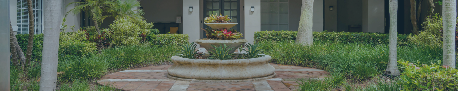 Courtyard area with pave stones, fountain,  bushes and landscaping
