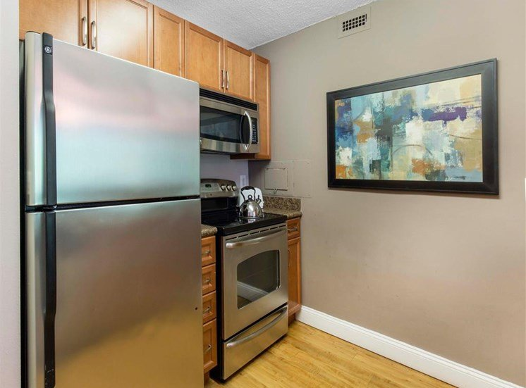 Kitchen with Brown Cabinets Stainless Steel Appliances and Grey Counters and Breakfast Bar with Decorative Items