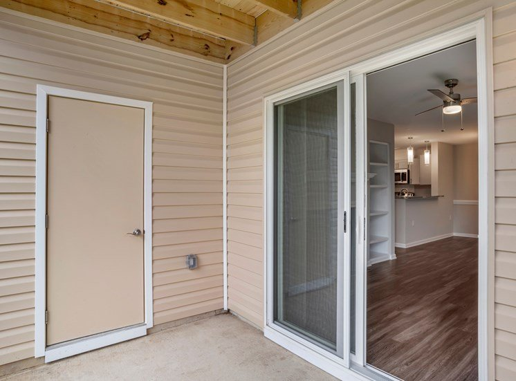 A patio area with concrete floors, tan siding of the exterior building, a door leading to storage, and a sliding glass door leading to the vacant living room with hardwood style flooring.
