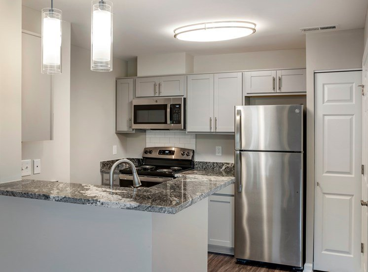 A renovated kitchen featuring hardwood style flooring, gray walls with white trim and doors, ash gray cabinets with brushed nickel pulls, granite countertops, stainless steel appliances, a single gooseneck faucet, and pendant lighting over the breakfast bar area. Appliances pictured include a refrigerator, stove/oven combo, and a built-in microwave.