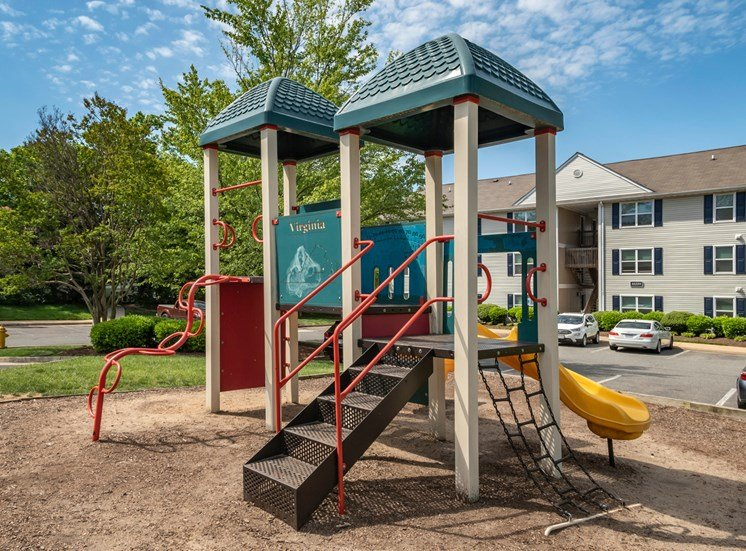 Playground with wood chips in court yard between buildings.