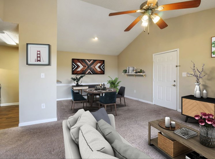 Carpeted Living Room with Virtually Staged Couch, Coffee Table, Entertainment Center and Dining Room with Virtually Staged Table Next to Kitchen