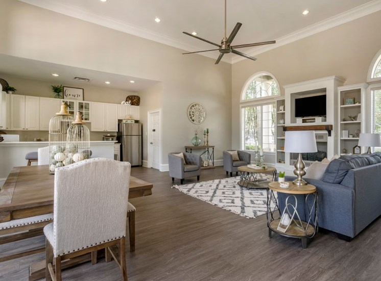 Clubhouse lounge with hardwood style flooring, couch, chairs, coffee table, rug, picnic table, fire place, book shelves, television, multi speed ceiling fan, and kitchen in the background