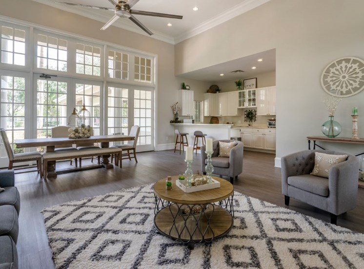 Clubhouse lounge with couch, chairs, coffee table, rug, picnic table, multi speed ceiling fan, large windows for natural lighting, and clubhouse kitchen in the background