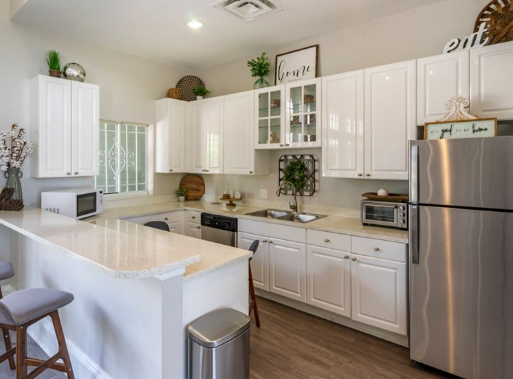 Clubhouse kitchen with stainless steel appliances, white cabinetry, and hardwood flooring