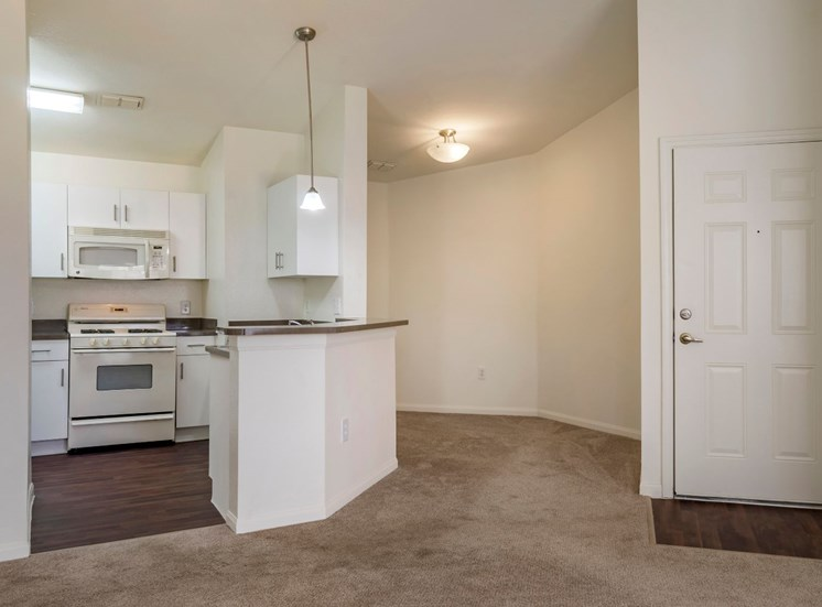 Fully equipped kitchen with white appliances and dining room with carpet flooring
