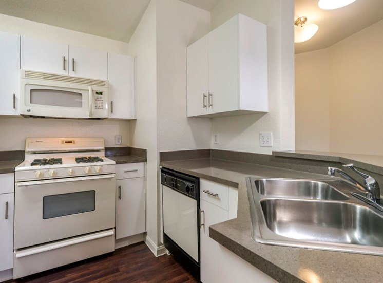 Fully equipped kitchen with white appliances, white cabinetry, and double basin sink