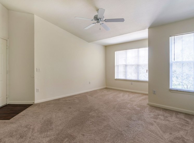 Spacious living room with carpet flooring, ceiling fan, and large windows for natural lighting