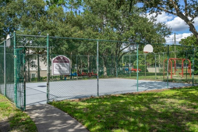 Outdoor basketball court surrounded by native landscaping and playground in the background