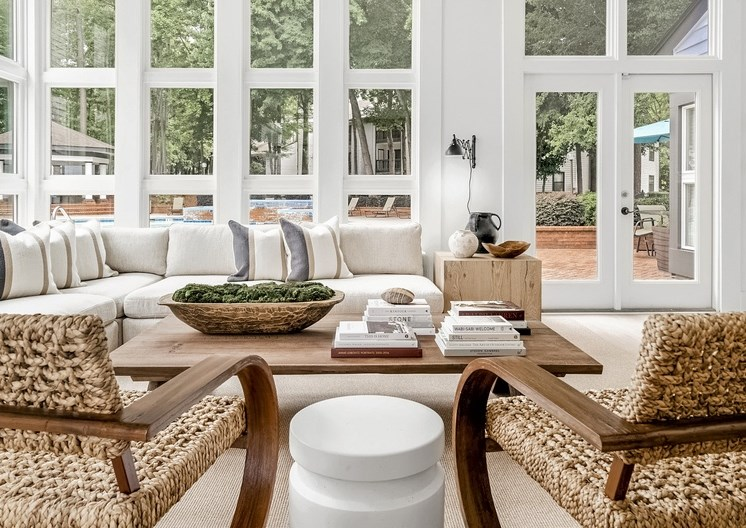 Clubhouse interior with large windows, accent chairs, wooden table, and a tan and white color scheme