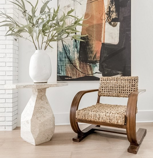 Wooden rocking chair, hardwood style flooring, and canvas artwork in the background