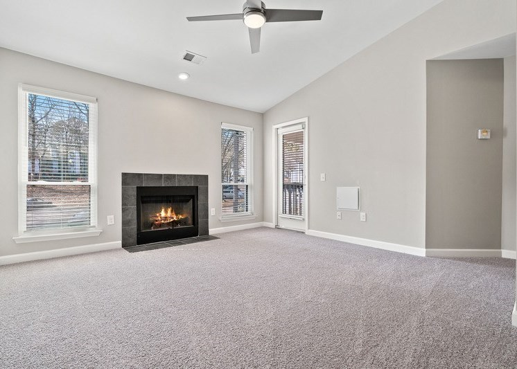 Living room with light gray carpet, ceiling fan, white walls, and fire place