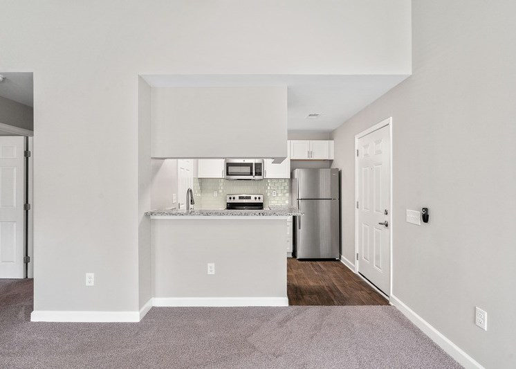 Fully equipped kitchen with brushed nickel appliances , hardwood style flooring, and view of living room