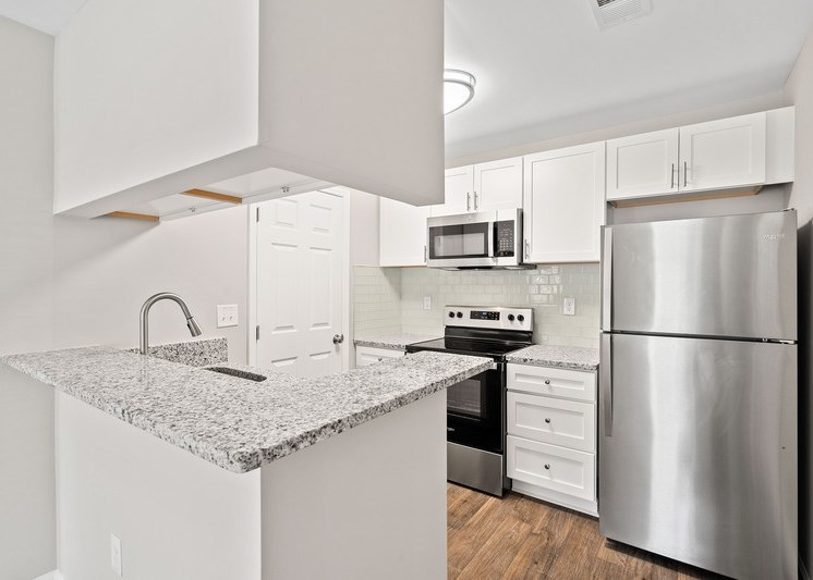 Fully equipped kitchen with brushed nickel appliances  and hardwood style flooring