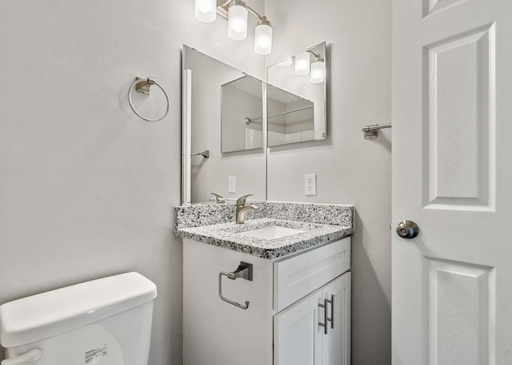 Bathroom with vanity lights, storage under the sink, and white walls