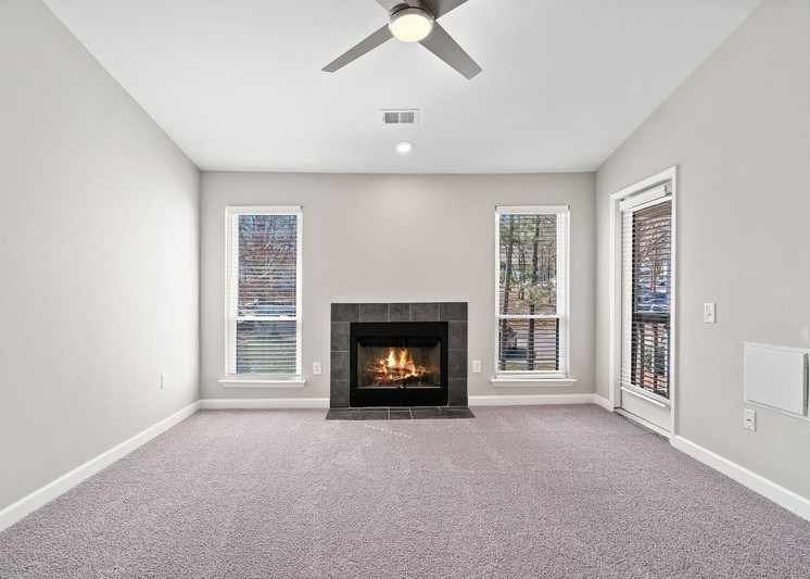 View of living room with fireplace, white walls and trim, and ceiling fan
