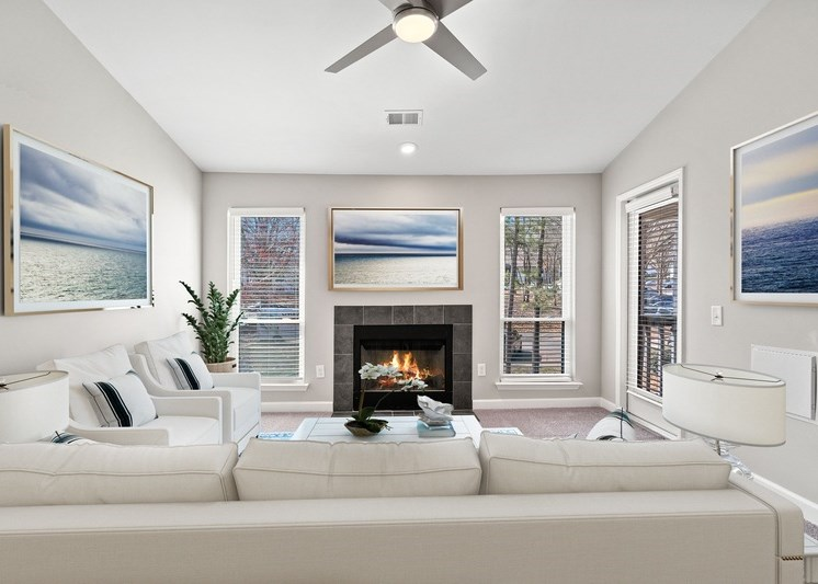 Virtual rendering of living room with white sofa, paintings on the walls, a fireplace, and a white and blue color scheme