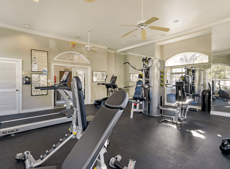 Fitness center with cardio equipment, large mirrors, and multi speed ceiling fan