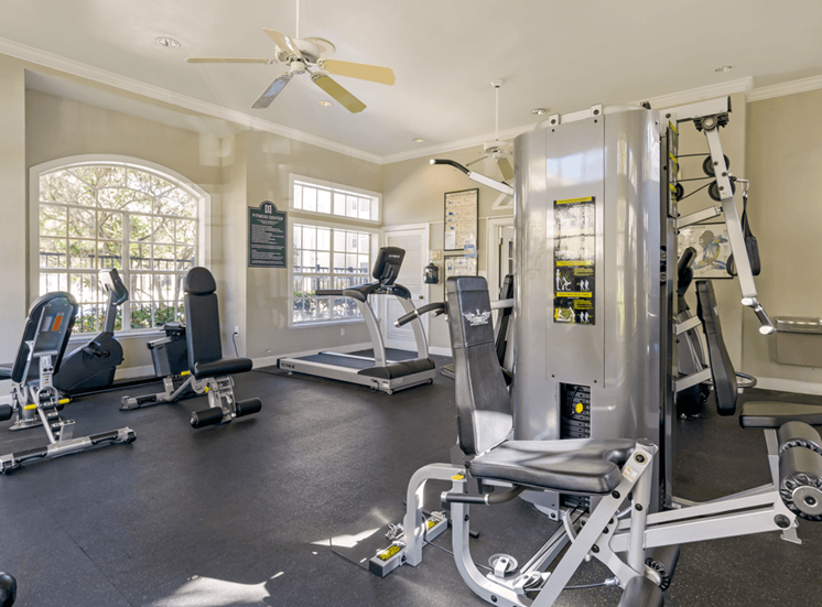 Fitness center with strength and conditioning equipment, multi speed ceiling fan, and large windows for natural lighting