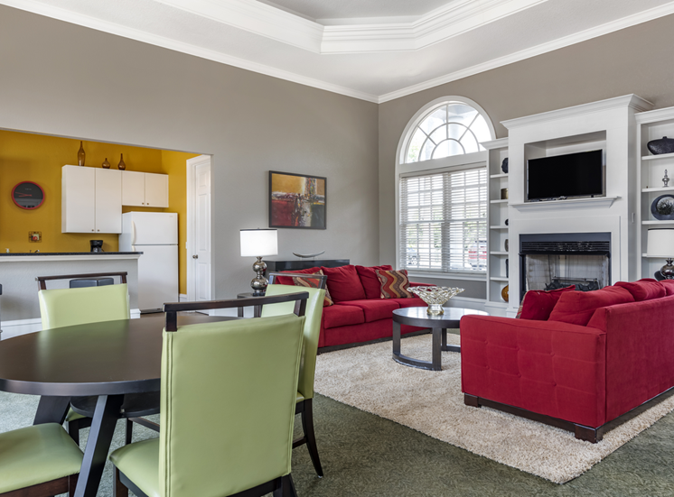 Clubhouse lounge with couches, chairs, coffee table, fireplace and windows for natural lighting