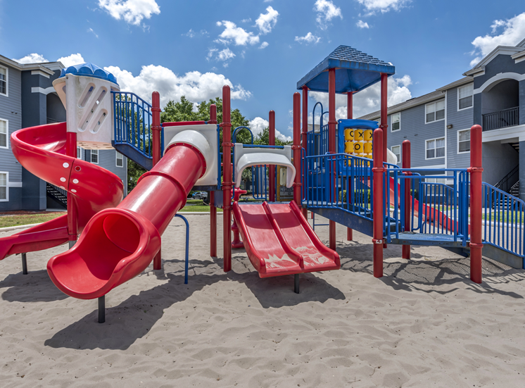 Outdoor playground equipped with two slides, monkey bars, and spiral latter