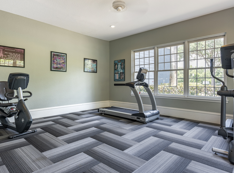 Fitness center with cardio equipment and large windows for natural lighting