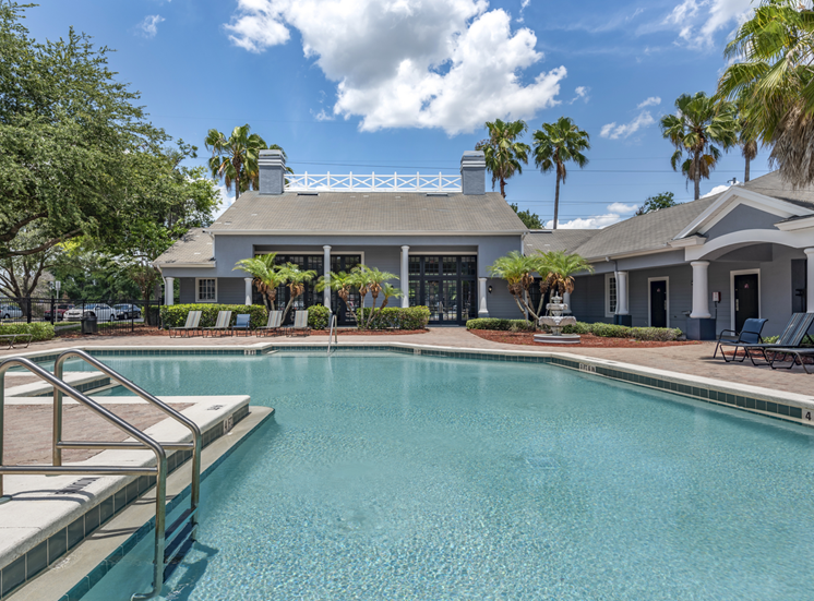 Swimming pool with lounge seating and clubhouse in the background surrounded by palm trees