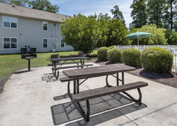 Community grilling and picnic areas featuring two picnic tables with built-in seating and two charcoal grills. The picnic area sits on a concrete pad and is surrounded by a grassy area. The fenced-in pool is located to the right side with an apartment building off in the distance. Shrubs and tall pine trees surround the area.