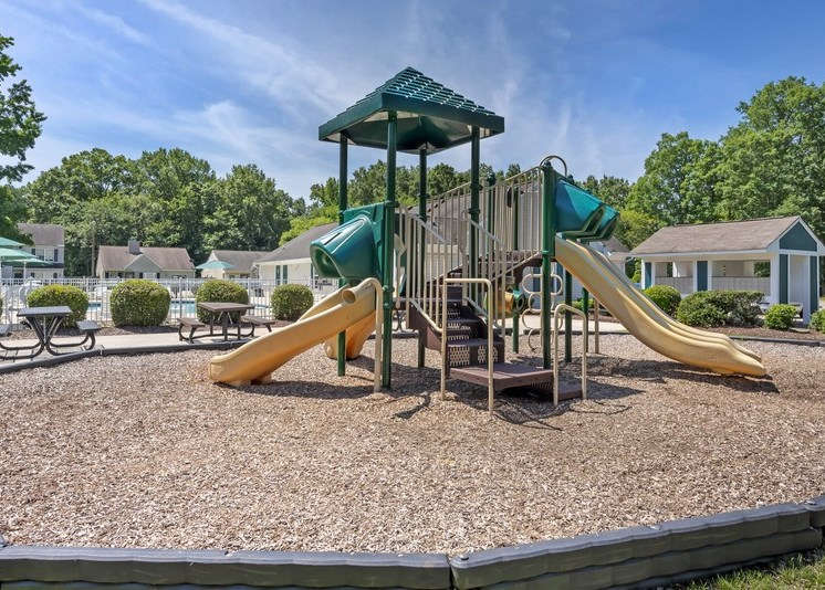 The community playground features a yellow, tan and green play structure with four slides of varying heights and slopes. The playground is surrounded by mulch and sits adjacent to the community pool to the left and the mailboxes to the right. Apartment buildings sit in the background with tall trees behind.