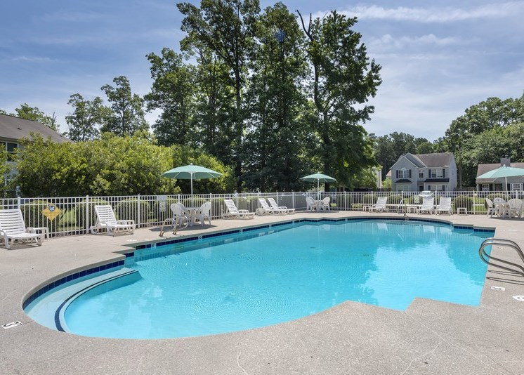 The community pool area is enclosed by a white fence, has a large sundeck area with white pool furniture including chaise lounge chairs, regular chairs, round tables, and three blue umbrellas. The exterior of the pool area is surrounded by grassy areas and mature trees. There are private homes located in the background.
