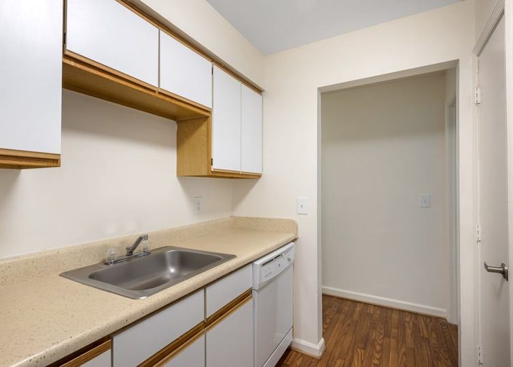 Vacant galley kitchen featuring hardwood-style flooring, white cabinets with wood trim, and a white dishwasher sitting adjacent to the kitchen pantry. Stainless steel sink sits atop beige countertop. The far end of the kitchen opens up to the bedroom hallway.