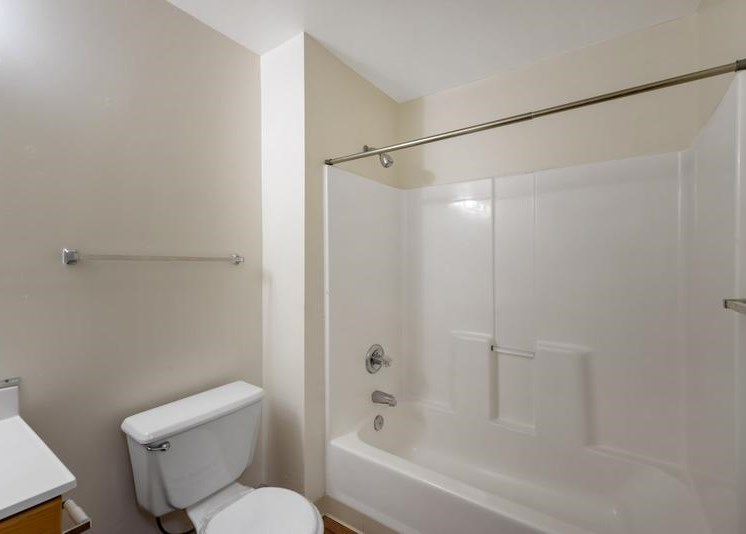 A vacant bathroom featuring off-white walls and a white ceiling. Brown wood-style flooring throughout. The bathroom also features a white shower/tub combo along with white bathroom vanity, white sink, and wood-colored trim. A large frameless bathroom mirror sits above the vanity  A Silver shower rod is in place for a curtain. A white toilet rests in between the vanity and tub.