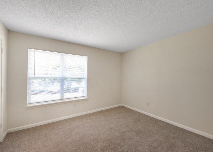 The vacant bedroom features tan carpet with beige walls and a white textured ceiling. A large window is centered along the back wall of the bedroom. White trim lines the walls along the bottom of the walls.