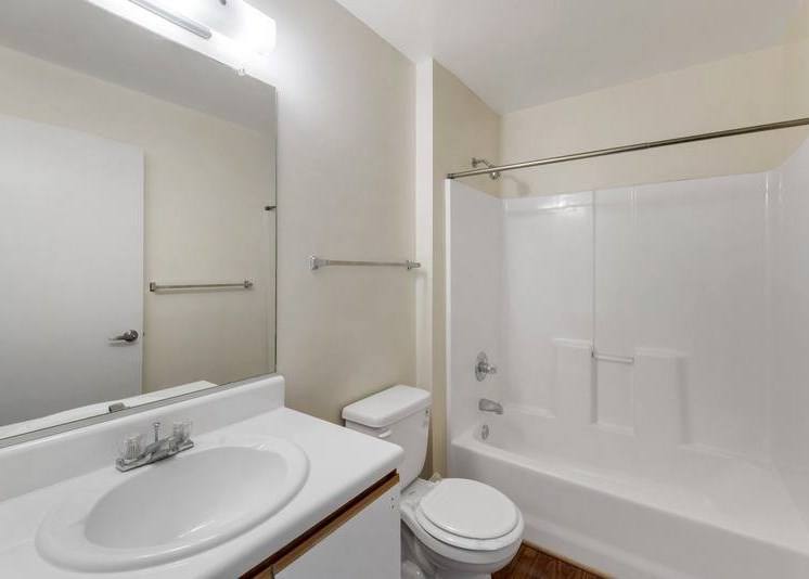 A vacant bathroom featuring off-white walls and a white ceiling. Brown wood-style flooring throughout. The bathroom also features a white shower/tub combo along with white bathroom vanity, white sink, and wood-colored trim. A large frameless bathroom mirror sits above the vanity A Silver shower rod is in place for a curtain.
