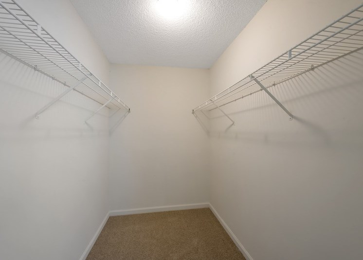 A vacant walk-in closet with carpet throughout, white walls, and white wired shelving installed on either side of the closet.