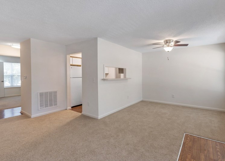 A vacant three-bedroom living room featuring white walls and ceilings. The vinyl floor at the entry gives way to a carpeted living room area and dining room area. There is a small cut-out with breakfast bar opening from the kitchen to the dining room. The kitchen features hardwood style flooring with white appliances and the second bedroom is located in the background.