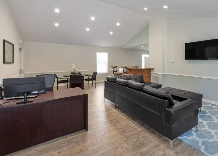The Leasing office features an upfront greeting desk with an adjacent waiting area featuring a black sofa with a matching ottoman that both rest on a blue area rug. A TV is mounted on the white wall in the waiting area. The greeting and waiting area opens up to a circular conference table with four chairs as well as a bar top with two bar stools.