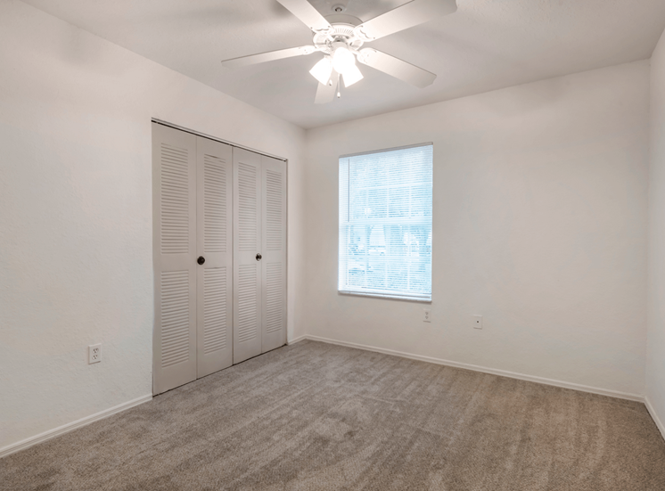 Bedroom with large reach-in closet, carpet flooring, and multi speed ceiling fan