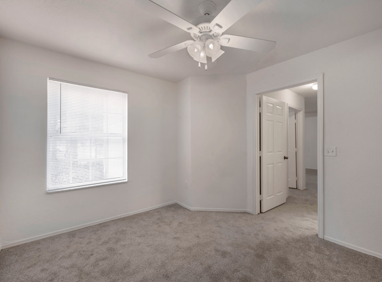 Bedroom with carpet flooring, multi speed ceiling fan, and large window for natural lighting