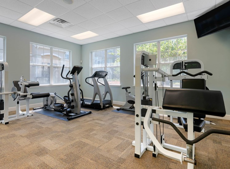 Fitness center equipped with strength training equipment, cardio equipment, and mounted tv