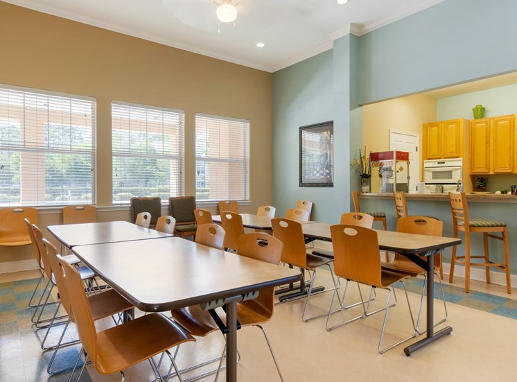 Resident Event and Recreation Room in Clubhouse with tables and chairs, and view of kitchen
