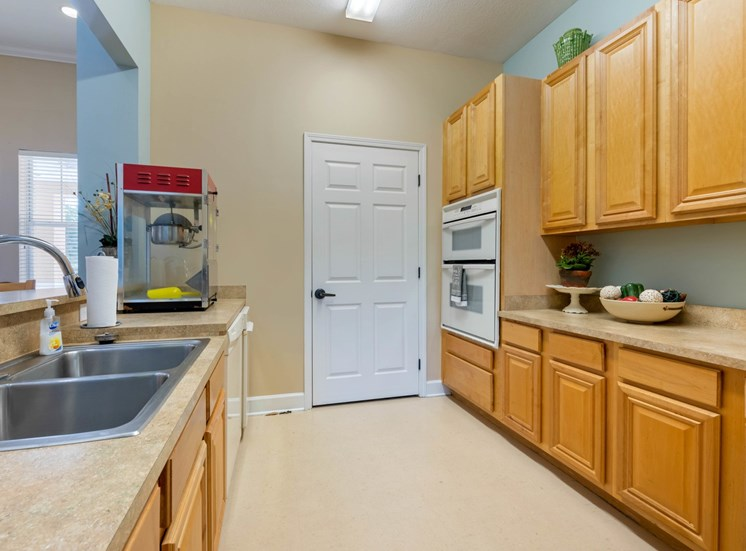 Clubhouse Kitchen with beige cabinets, white appliances, and breakfast bar and popcorn machine