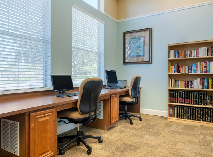 Business center with 2 desktop computers with a book shelf in the background