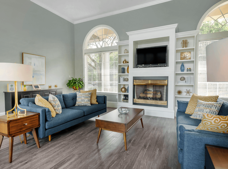 Clubhouse lounge with hardwood style flooring, couches, chairs, coffee table, fire place, and wall mounted television
