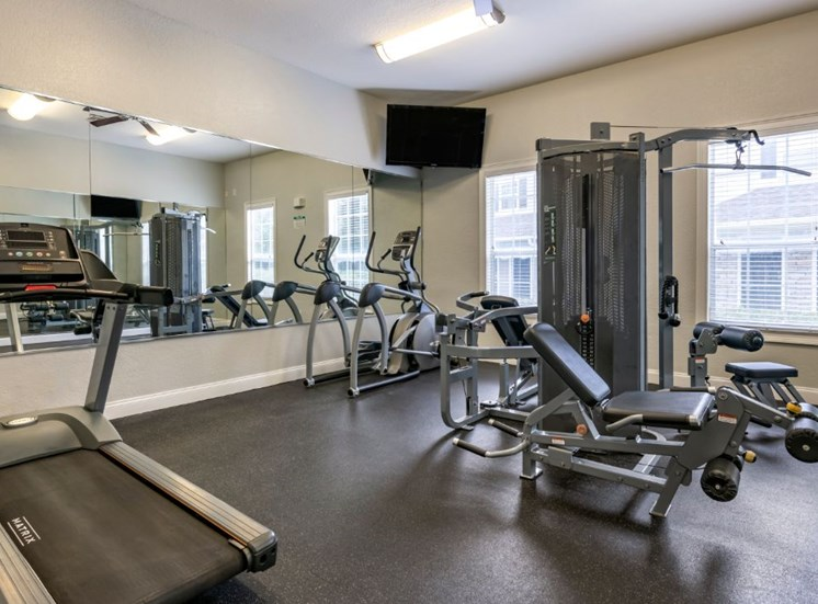 Fitness center with strength and conditioning equipment, cardio equipment, and large mirrors