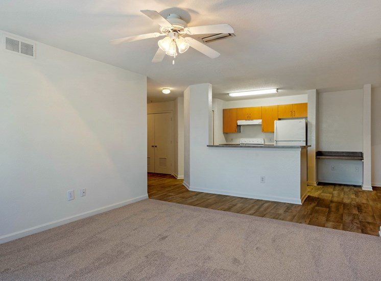 Carpeted living room with white walls and ceiling fan with the kitchen and built in desk in the background