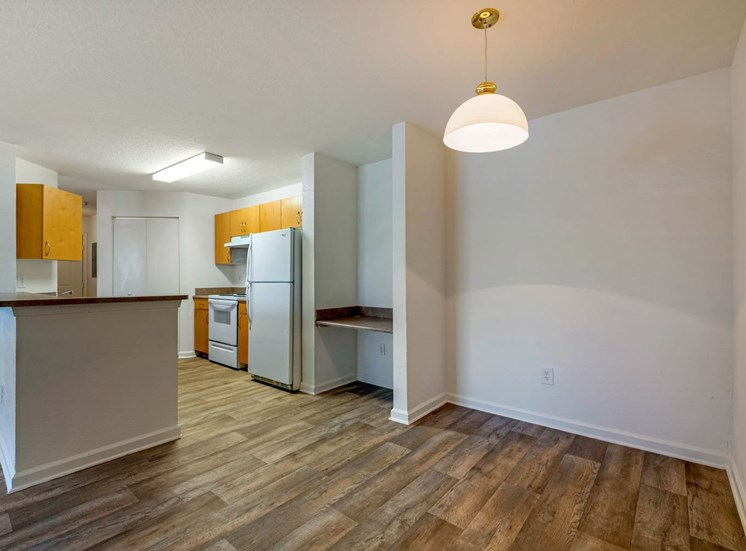 Dining Room with wood floors, white walls, and built in desk with view of the kitchen in the back